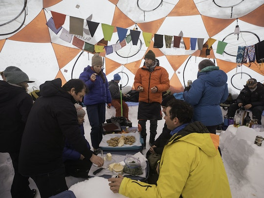 Eveyone eating food inside the tent