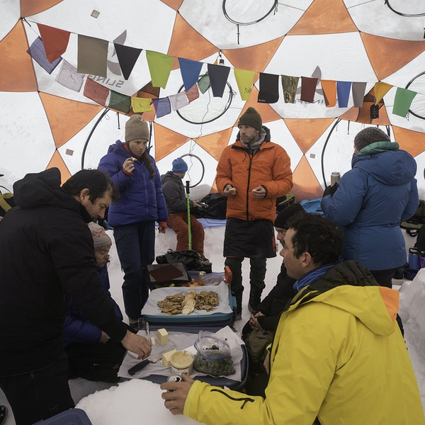 Everyone eating food inside the tent